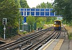 London Overground train approaching Kew Gardens station from south.jpg
