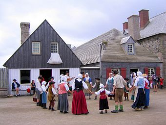 Costumed interpreters perform a dance in the street at Fortress Louisbourg.