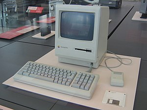 Macintosh Plus monitor, keyboard, mouse, and floppy disk in a museum display case