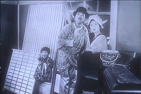 A young girl, man, and woman standing outside of a house, all looking up in the sky. The girl, on the left, is smiling and pointing skyward, the man wears a bowler hat and holds a short broom over his shoulder; the woman wears a kerchief around her head. They are surrounded by domestic objects as if just moving into or out of the house.