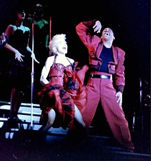 Madonna wearing a magenta jacket and black pants singing to a microphone held in her right hand