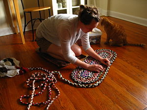 Braided rug - A woman making a braided rug.
