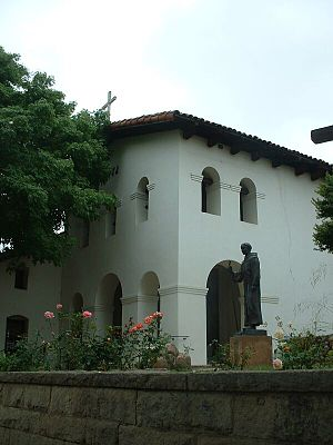 San Luis Obispo County, California - The entrance lobby and belfry of the Mission San Luis Obispo de Tolosa. A statue of Fray Junípero Serra stands outside the church.