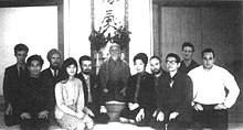 Black-and-white photograph of a group of people kneeling around an elderly Japanese man