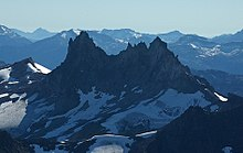 A dark rugged mountain rising over glacial ice in the foreground and glaciated mountains in the background.