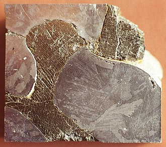 Troilite - Polished and etched surface of the Mundrabilla meteorite from Australia. The darker brownish areas with striations are troilite with exolved daubréelite.