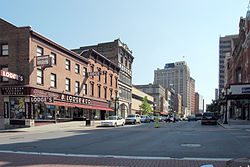 "A view down an urban street in a well-developed area. There are lower buildings in the foreground, including one with ""B. Lodge & Co."" prominently displayed on it at the left, across the intersection from the camera. In the rear are taller ones."