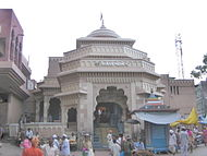 "Chief (eastern) entrance of the temple, with houses the ""Namdeva chi Payari"". The small blue temple in front of the gate is saint Chokhamela's memorial."