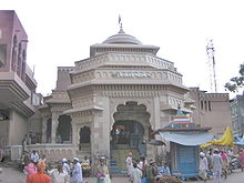 An elaborate, carved entrance to a Hindu temple whose canopy is visible at the top of the image. The entrance section is polygonal with arches and there is a stone staircase leading into the grey/cream coloured structure. Several pilgrims are seen in the foreground, as is a stall.