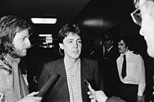 Paul McCartney being interviewed by two reporters holding microphones.