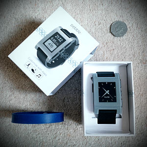 Pebble (watch) - Pebble smartwatch size compared to UK's 50p coin and standard silicone wristband.