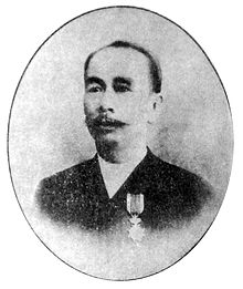 A black and white photograph of a Chinese man in a suit, looking forward