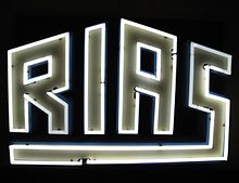 "Stylized ""RIAS"" neon sign against black background"