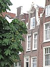 foto van Huis met gave ingezwenkte halsgevel waarin deuromlijsting met deur en snijraam