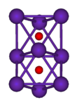 The ball-and-stick diagram shows two regular octahedra which are connected to each other by one face. All nine vertices of the structure are purple spheres representing rubidium, and at the centre of each octahedron is a small red sphere representing oxygen.