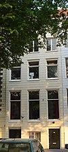 Gepleisterd koopmanshuis met eenvoudige lijstgevel. Onder de kroonlijst liggende vensters, gescheiden door triglyfen
