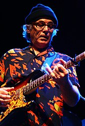 A man in a printed shirt wearing eyeglasses and a cap on his head, playing a guitar