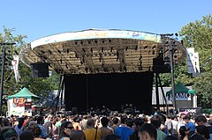 The covered stage known as Summerstage with a band entertaining a crowd of people