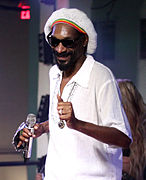 Snoop Dogg with a beanie in a white collared shirt