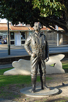 Bronze, life size statue of a man wearing the clothes and equipment of an aviator. A street and buildings can be seen in the background.