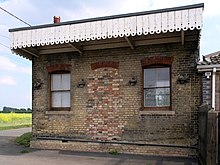 small disused railway station looking from the other side of the track two windows bricked-up doorway roof bordered by white painted edges