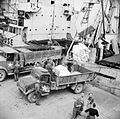 Supplies being unloaded from a ship at the Mulberry artificial harbour at Arromanches in Normandy, July 1944. B7231.jpg