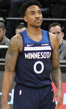 Hip high portrait of man with dark hair and tattooed arms wearing navy blue Timberwolves uniform