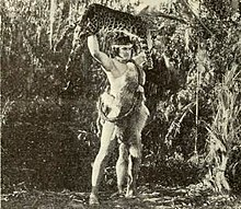 Tarzan holding a tiger corpse above his head