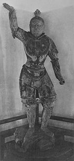 Tamonten, un des Quatre Rois célestes in the Kaidan Hall. Portrait of a statue in front view. The right arm is raised, the hair sculpted with a top knot and the breast with armour. Narrow slit eyes and a facial expression as if frowning.