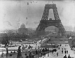 A black and white image showing the Eiffel Tower under construction.