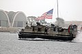 US Navy 041002-N-1722M-005 A Landing Craft Air Cushion (LCAC), assigned to the amphibious assault ship USS Tarawa (LHA 1), passes in front of Naval Base Coronado-Naval Air Station North Island with the American Flag in the back.jpg