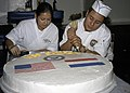 US Navy 050228-N-0050M-001 Culinary Specialist 3rd Class Adriana Andrade, left, smoothes-out the sides as Culinary Specialist Seaman Jonathan Nicho spells out Saipan on a cake.jpg