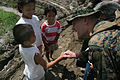 US Navy 060219-M-8084P-048 Civil military operations chief for the 31st Marine Expeditionary Unit spends a few moments Feb. 19 with children from the area around the devastated town of Guinsahugon.jpg