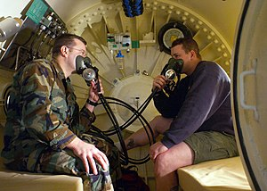 Hyperbaric treatment schedules - Navy Divers test built-in breathing masks inside a recompression chamber