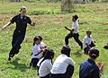 US Navy 071127-N-5348D-002 Electronics Technician 3rd Class Rosemary Colberte stationed aboard the amphibious assault ship USS Essex (LHD 2) runs from a Hen Sen Krong Primary School student during a game of Duck, Duck, Goose.jpg