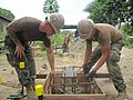 US Navy 100825-N-5390M-032 Steelworker 3rd Class Henry O'Hair, left, and Steelworker Anthony Thompson, both assigned to Amphibious Construction Battalion (ACB) 1 based in San Diego, lower a reinforcing steel cage into a ground.jpg