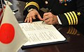 US Navy 101117-N-8730P-121 Capt. Eric Gardner, commanding officer of Naval Air Facility Atsugi, signs a memorandum of understanding at Fujisawa Cit.jpg