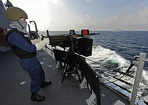 US Navy 120105-N-VH839-025 Fire Controlman 2nd Class Milo Wilson mans a double-mounted .50-caliber machine gun.jpg