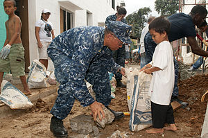US Navy 120201-N-OH194-042 Senior Chief Electrician's Mate Crisanto Flores removes construction debris during a community service project in the vi.jpg