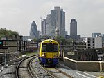 A Class 378 train at Hoxton, with the City of London skyline in background in 2010