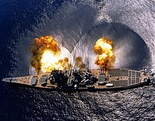 An overhead view of a battleship, showing the ship's teardrop shaped hull. Nine gun barrels on three turrets are pointed to the top of the image, with smoke and fire visible form all nine gun barrels and a concussive effect on the water below the guns. Visible from the overhead image are the 8 armored box launchers for the battleship's 32 Tomahawk Missiles.