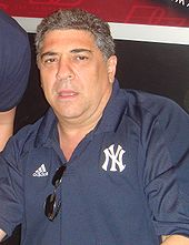 A man with graying hair wearing a navy blue shirt which is holding his sunglasses. Logos for Adidas and the New York Yankees appear on his shirt