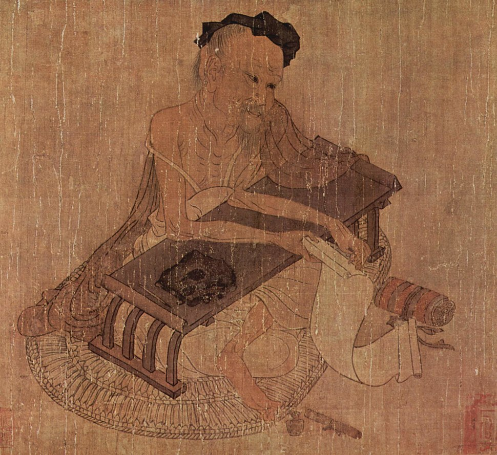 Elderly Chinese man, seated at a low writing desk and holding a scroll