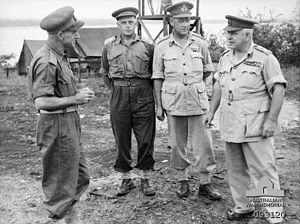 Four men in uniforms wearing peaked caps stand around talking. In the background are some tents and scaffolding.