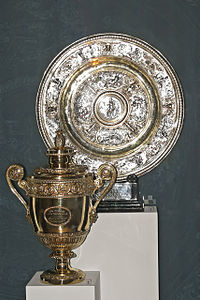 A golden trophy, in the shape of a loving-cup, next to a silver plate
