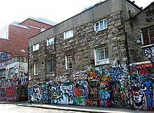 A three-storey stone-faced building. The first level is decorated with colourful graffiti.