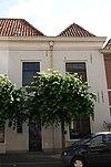 foto van Huis onder haaks gericht schilddak, met geprofileerde kroonlijst en gecementeerde gevel