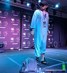 Photograph of a man in a Kigurumi with a microphone, vape, and Mountain Dew on the floor.
