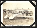 """Camp Borden""- photograph of a Curtiss JN-4 aircraft (number C502, with fleur-de-lis and roundel insignia) on the ground next to a hangar building. There is one man in the rear seat, one holding the (7980804878).jpg"