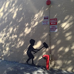 "Better Out Than In - ""Hammer Boy"" was the 20th installment, located on the Upper West Side. Utilizing an existing siamese connection fire hydrant, it depicts a child playing a high striker."